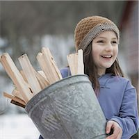 An organic farm in winter in New York State, USA. A girl carrying a bucket full of kindling and firewood. Stock Photo - Premium Royalty-Freenull, Code: 6118-07354219