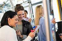 New York City park. People, men and women on a city bus. Public transport. Two women looking at a handheld digital tablet. Stock Photo - Premium Royalty-Freenull, Code: 6118-07354343