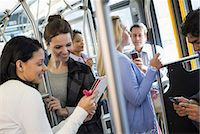 New York City park. People, men and women on a city bus. Public transport. Two women looking at a handheld digital tablet. Stock Photo - Premium Royalty-Freenull, Code: 6118-07354344