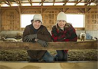 An Organic Farm in Winter in Cold Spring, New York State. A farmer and a woman standing by a pen full of sheep. Stock Photo - Premium Royalty-Free, Artist: Westend61, Code: 6118-07354439