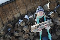 Winter scenery with snow on the ground. A girl collecting firewood from the log pile. Stock Photo - Premium Royalty-Freenull, Code: 6118-07354458
