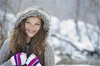 Winter scenery with snow on the ground. A young girl in a woolly hat with ski gloves on. Stock Photo - Premium Royalty-Freenull, Code: 6118-07354469