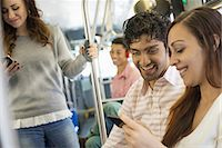 Urban Lifestyle. A group of people, men and women on a city bus, in New York city. A man wearing headphones and a couple looking at a mobile phone. Stock Photo - Premium Royalty-Freenull, Code: 6118-07354529