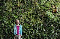 Outdoors in the city in spring. An urban lifestyle. A young girl standing in front of a wall covered with ferns and climbing plants. Stock Photo - Premium Royalty-Freenull, Code: 6118-07354753