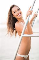 Smiling Woman Wearing Bikini Leaning on Railing of Stairway Stock Photo - Premium Rights-Managednull, Code: 822-07355518
