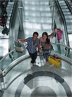 Couple holding shopping bags on balcony in mall Stock Photo - Premium Royalty-Freenull, Code: 635-07365307