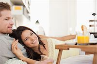 Couple laying in bed having breakfast Stock Photo - Premium Royalty-Freenull, Code: 635-07365332