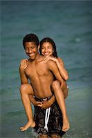 preteen girl topless - Brother and Sister piggy back in ocean Stock Photo - Premium Royalty-Freenull, Code: 618-07396437