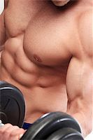 Fitness. Powerful guy with a dumbbell Stock Photo - Royalty-Freenull, Code: 400-07418233