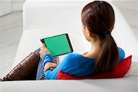 diego_cervo (artist) - portrait of beautiful asian girl using tablet pc with green screen, sitting on sofa at home Stock Photo - Royalty-Freenull, Code: 400-07419543