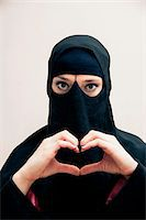restrained - Close-up portrait of young woman wearing black, muslim hijab and muslim dress, making heart shape with hands, looking at camera, eyes showing eye makeup, studio shot on white background Stock Photo - Premium Royalty-Freenull, Code: 600-07434928