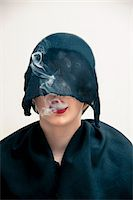 restrained - Close-up portrait of young woman wearing black, muslim dress and black, hijab covering part of head, while blowing smoke from red lips, studio shot on white background Stock Photo - Premium Royalty-Freenull, Code: 600-07434931