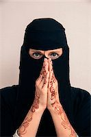 restrained - Close-up portrait of woman wearing black muslim hijab and muslim dress looking at camera, with hands praying and showing arms and hands painted with henna in arabic style, studio shot on whtie background Stock Photo - Premium Royalty-Freenull, Code: 600-07434938