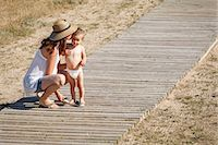 Mother and son standing on boardwalk, kissing cheek Stock Photo - Premium Royalty-Freenull, Code: 649-07436379