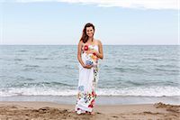 Pregnant woman standing on beach, hands on stomach Stock Photo - Premium Royalty-Freenull, Code: 649-07436421