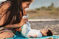 Mother looking down at baby lying on rug Stock Photo - Premium Royalty-Free, Artist: Cultura RM, Code: 649-07436431