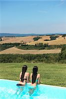 Teenage girls in swimming pool looking at view of Tuscany, Italy Stock Photo - Premium Royalty-Freenull, Code: 649-07436493