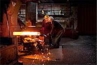 people working in factory - Forge workers pre form red hot billet into flight bar (mining component) on hammer Stock Photo - Premium Royalty-Freenull, Code: 649-07436911