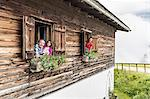 Portrait of family at chalet windows, Achenkirch,  Tyrol, Austria