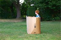 Young boy watching from cardboard box in garden Stock Photo - Premium Royalty-Freenull, Code: 649-07437210