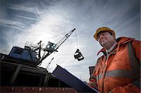 supervising - Low angle view of load master checking ship loading Stock Photo - Premium Royalty-Freenull, Code: 649-07437248