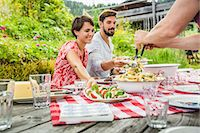 Group of friends sharing picnic lunch, Tyrol, Austria Stock Photo - Premium Royalty-Freenull, Code: 649-07437630