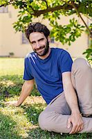 Portrait of mid adult man sitting on grass Stock Photo - Premium Royalty-Freenull, Code: 649-07437644
