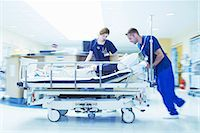 people hospital - Two medics pushing gurney in hospital emergency room Stock Photo - Premium Royalty-Freenull, Code: 649-07437681