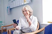 results - Mature female patient looking at mobile phone in hospital waiting room Stock Photo - Premium Royalty-Freenull, Code: 649-07437694