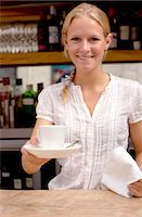 Portrait of young waitress holding coffee at kitchen counter Stock Photo - Premium Royalty-Free, Artist: Blend Images, Code: 649-07437823