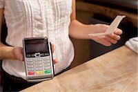 Close up of waitress holding credit card reader at kitchen counter Stock Photo - Premium Royalty-Freenull, Code: 649-07437825