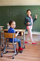 Girl by blackboard and sister at desk Stock Photo - Premium Royalty-Freenull, Code: 649-07437855