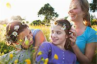 Mother tying daisy chain around daughter's head Stock Photo - Premium Royalty-Freenull, Code: 649-07437900