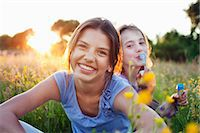 Portrait of girls sitting in field, one blowing bubbles Stock Photo - Premium Royalty-Freenull, Code: 649-07437906
