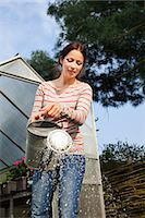 Young woman using watering can Stock Photo - Premium Royalty-Freenull, Code: 649-07437931