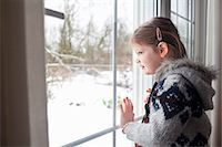 Young girl looking out of window at garden in snow Stock Photo - Premium Royalty-Freenull, Code: 649-07437955