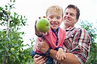 family apple orchard - Farmer and son picking apples from tree in orchard Stock Photo - Premium Royalty-Freenull, Code: 649-07437983