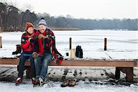 Couple sitting on pier having hot drink Stock Photo - Premium Royalty-Freenull, Code: 649-07437999