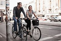 Happy couple riding bicycles on city street Stock Photo - Premium Royalty-Freenull, Code: 698-07439392