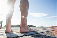 Low section of mature man standing on boardwalk Stock Photo - Premium Royalty-Freenull, Code: 698-07439512