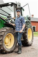 Full length portrait of farmer with hammer standing by tractor on farm Stock Photo - Premium Royalty-Freenull, Code: 698-07439548