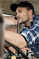 Thoughtful farmer driving tractor Stock Photo - Premium Royalty-Freenull, Code: 698-07439549