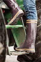 farmhand (female) - Low section of female farmer entering tractor Stock Photo - Premium Royalty-Freenull, Code: 698-07439556