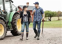 Full length of farming couple walking by tractor Stock Photo - Premium Royalty-Freenull, Code: 698-07439557