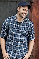 Happy farmer standing with hands in pockets against barn door Stock Photo - Premium Royalty-Freenull, Code: 698-07439567