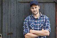 Portrait of confident farmer standing arms crossed against barn door Stock Photo - Premium Royalty-Freenull, Code: 698-07439568