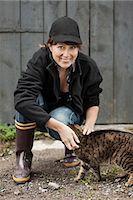 farmhand (female) - Full length portrait of female farmer petting cat against barn Stock Photo - Premium Royalty-Freenull, Code: 698-07439570