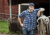 Portrait of confident farmer leaning on railing Stock Photo - Premium Royalty-Freenull, Code: 698-07439572