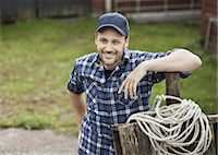 Smiling farmer looking away while leaning on railing at farm Stock Photo - Premium Royalty-Freenull, Code: 698-07439574