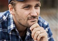 Close-up of thoughtful farmer with hand on chin looking away Stock Photo - Premium Royalty-Freenull, Code: 698-07439576
